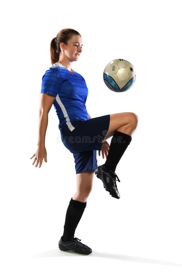 Kvinnlig fotbollspelare som studsar bollen fotografering för bildbyråer