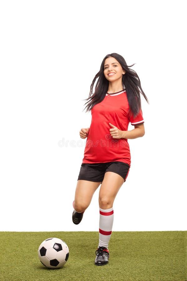 Kvinnlig fotbollsspelare som sparkar en boll på ett fält royaltyfri foto