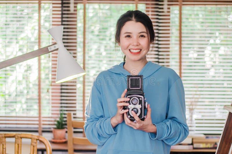 Kvinnlig fotograf för stilfull tappning som rymmer hennes gamla tvilling- linskamera till hennes bröstkorg, som hon komponerar he fotografering för bildbyråer
