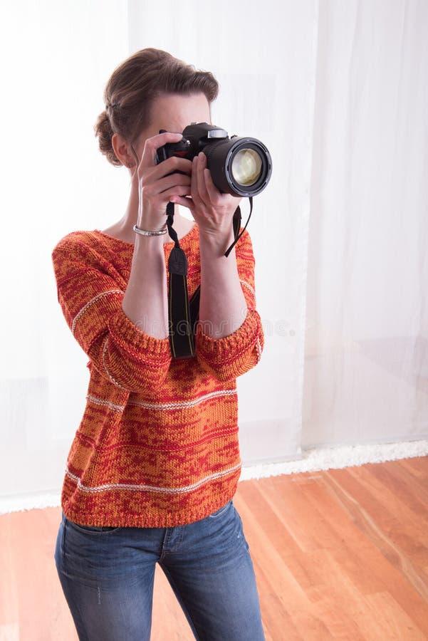 Kvinnlig fotograf i studion som tar bilder royaltyfri foto