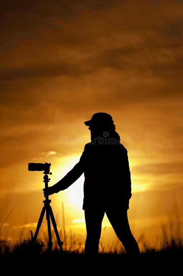 Kvinnlig fotograf med kameran på sunsetlight arkivfoton