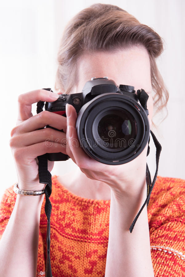 Kvinnlig fotograf på arbete med kameran royaltyfri foto