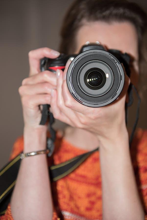 Kvinnlig fotograf på arbete med kameran arkivbild