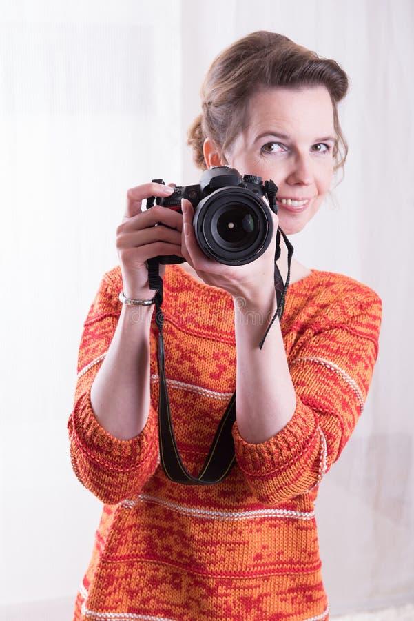 Kvinnlig fotograf på arbete med kameran arkivbilder