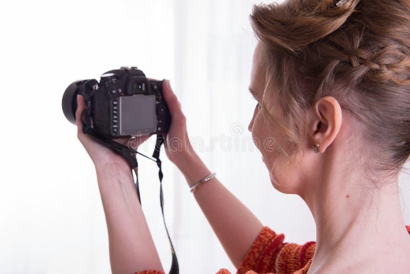 Kvinnlig fotograf på arbete med kameran arkivfoto