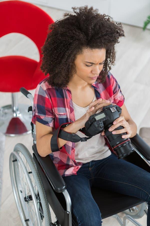 Kvinnlig fotograf på rullstolen genom att använda den mirrorless kameran royaltyfria foton