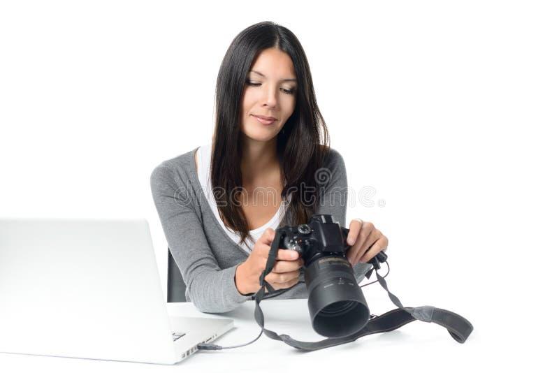 Kvinnlig fotograf som kontrollerar en bild på en kamera arkivbilder
