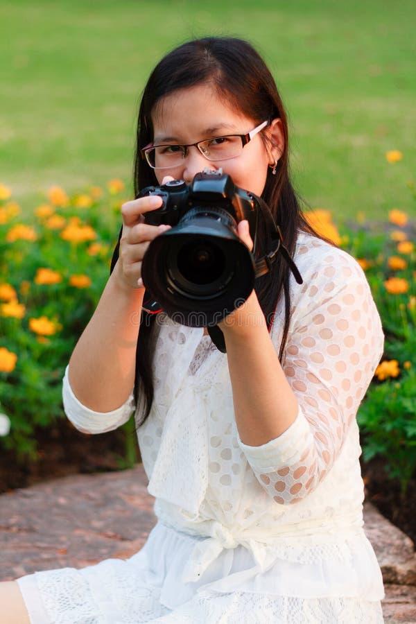 Kvinnlig fotograf som rymmer hennes kamera royaltyfri bild