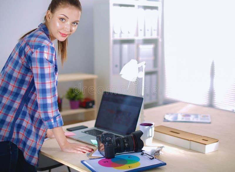 Kvinnlig fotograf som står det near skrivbordet med bärbara datorn royaltyfri bild