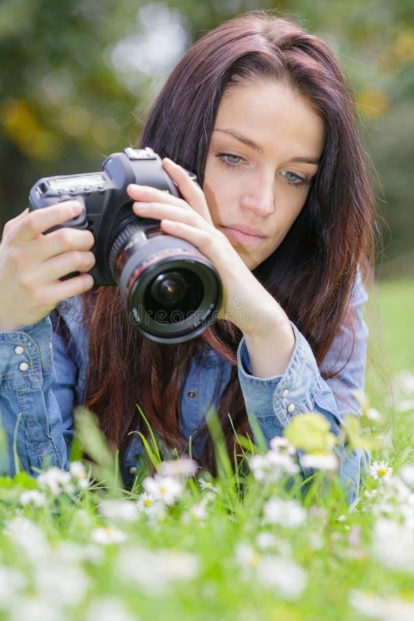 Kvinnlig fotograf som tar fotoblomningrosor i sommardag fotografering för bildbyråer