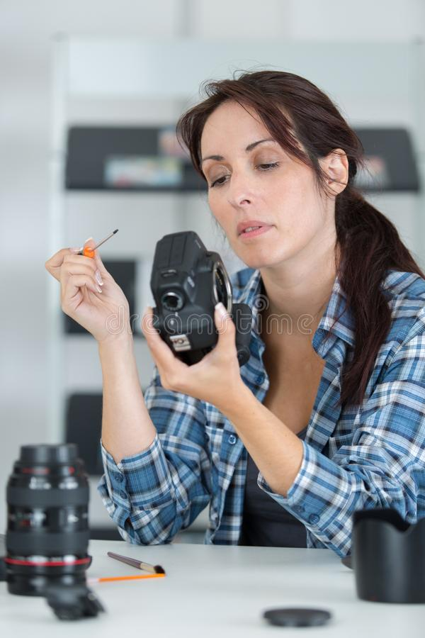 Kvinnlig fotograf som trimmar kameran på studion royaltyfri foto