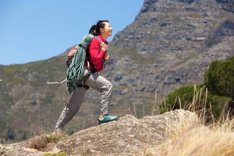 Kvinnlig fotvandrare för full längd som promenerar klippan med repet arkivfoton