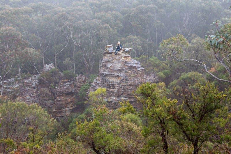 Kvinnlig fotvandrare i blåa berg överst av pagoden i mist och dimma arkivbilder
