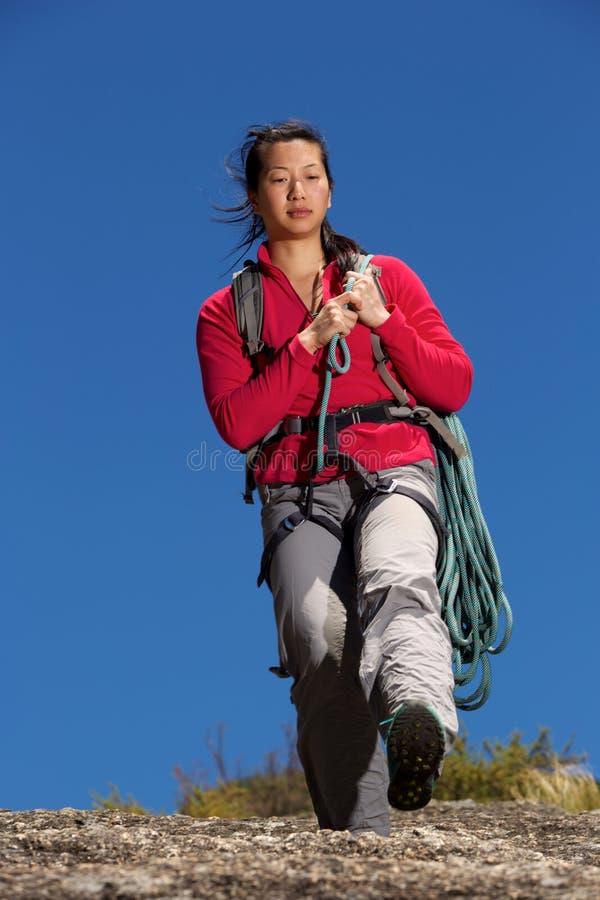 Kvinnlig fotvandrare som går ner berget med repet arkivbild