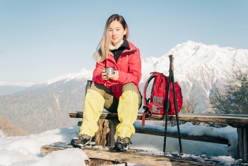 Kvinnlig fotvandrare som vilar i vinter royaltyfri fotografi
