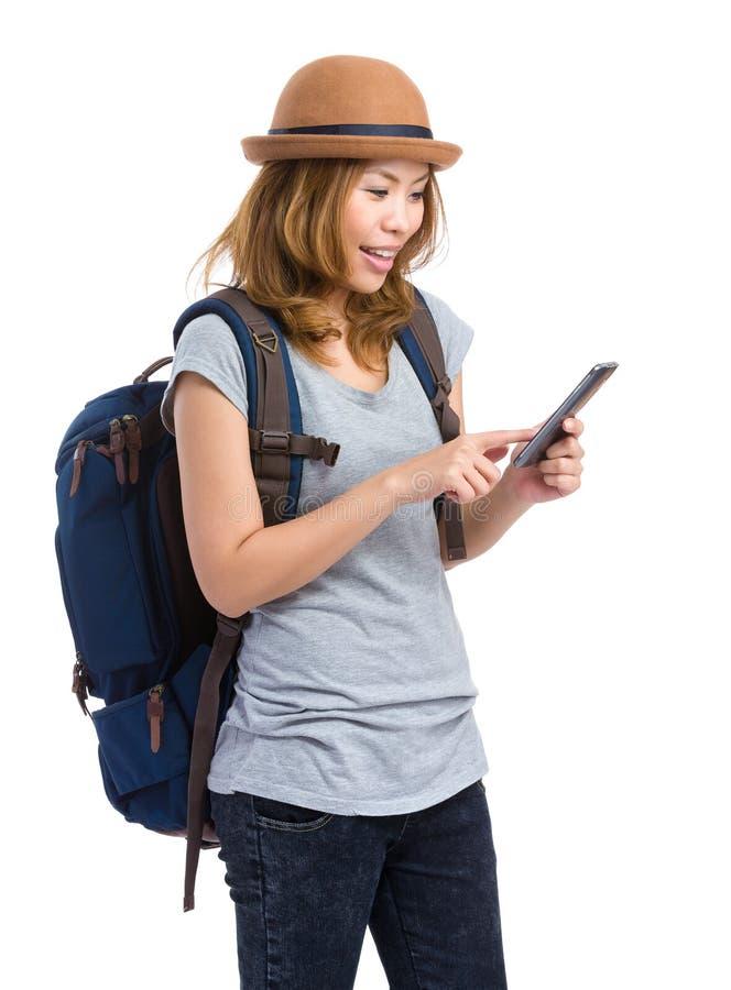 Kvinnlig fotvandrareblick på mobiltelefonen arkivfoto