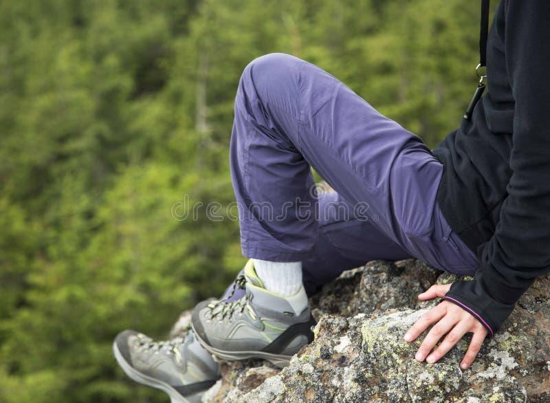 Kvinnlig fotvandrarekropp på berget arkivbild