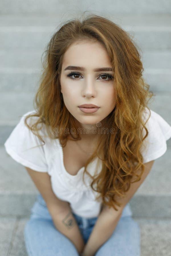 Kvinnlig framsidastående av den nätta unga attraktiva kvinnan i trendig vit t-skjorta i jeans med härliga bruna ögon utomhus royaltyfri bild