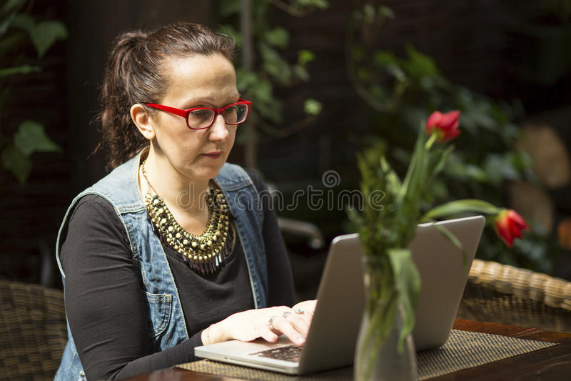 Kvinnlig freelancer med en bärbar dator i ett sommarkafé Arbeta arkivbild