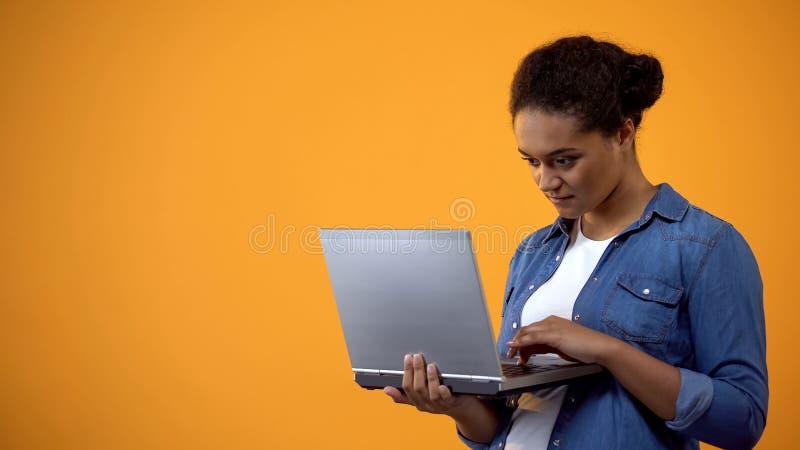 Kvinnlig freelancer som skriver b?rbar datortangentbordet p? gul bakgrund, bloggerstolpe royaltyfri fotografi