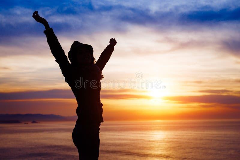 Kvinnlig frihet och lycka på solnedgång in mot havet royaltyfria bilder