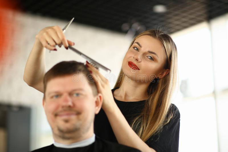 Kvinnlig fris?r Combing Male Client i salong arkivbild