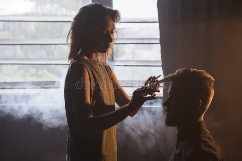 Kvinnlig frisör som klipper modernt hipsterhår arkivfoton