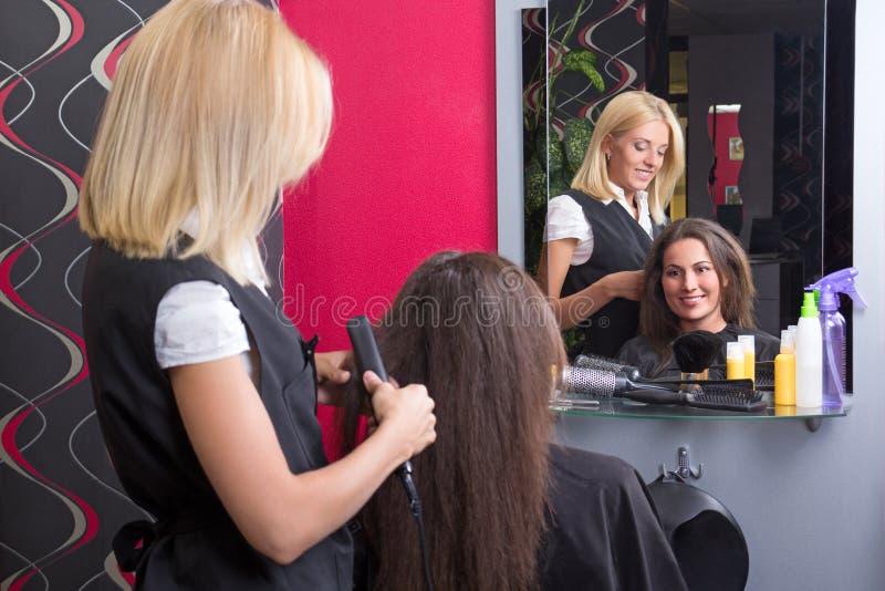 Kvinnlig frisör som rätar ut kvinnas hår i skönhetsalong royaltyfri bild