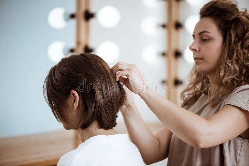 Kvinnlig frisördanandefrisyr till brunettflickan i skönhetsalong arkivfoton