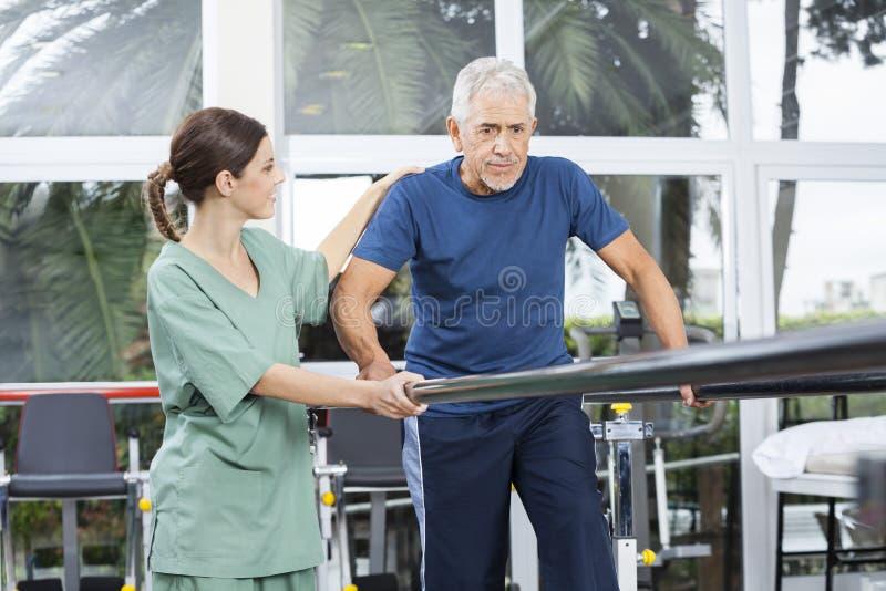 Kvinnlig fysioterapeut Motivating Senior Patient som Between går royaltyfri bild