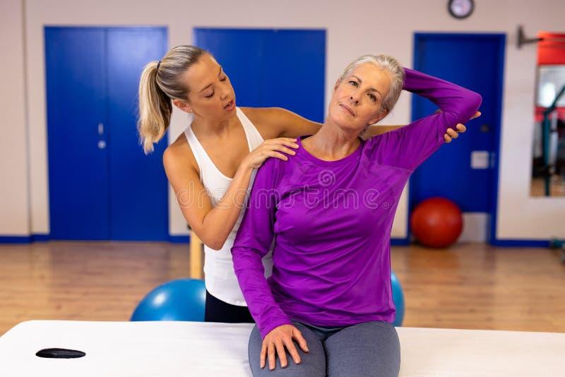 Kvinnlig fysioterapeut som ger armmassage till den aktiva höga kvinnan i sportmitt arkivbilder