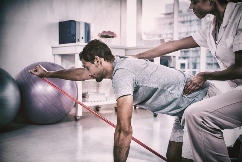 Kvinnlig fysioterapeut som hjälper en manlig patient, medan öva fotografering för bildbyråer