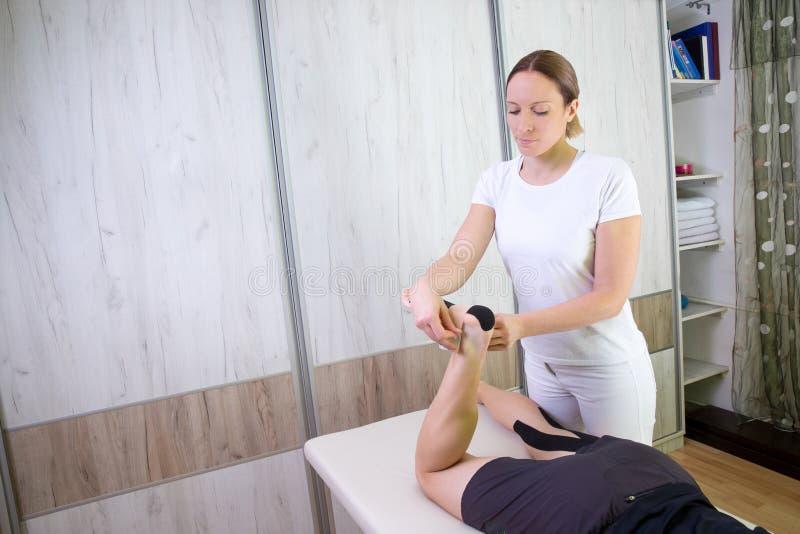 Kvinnlig fysioterapeut som sätter kinesiobandet royaltyfria foton