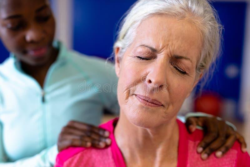 Kvinnlig fysioterapeut som tillbaka ger massage till den aktiva höga kvinnan i sportmitt arkivbild