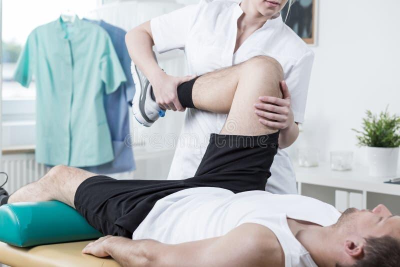 Kvinnlig fysioterapeututbildning med mannen royaltyfria bilder