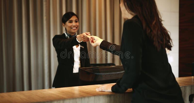 Kvinnlig gäst som tar rum det nyckel- kortet på incheckningskrivbordet arkivbild