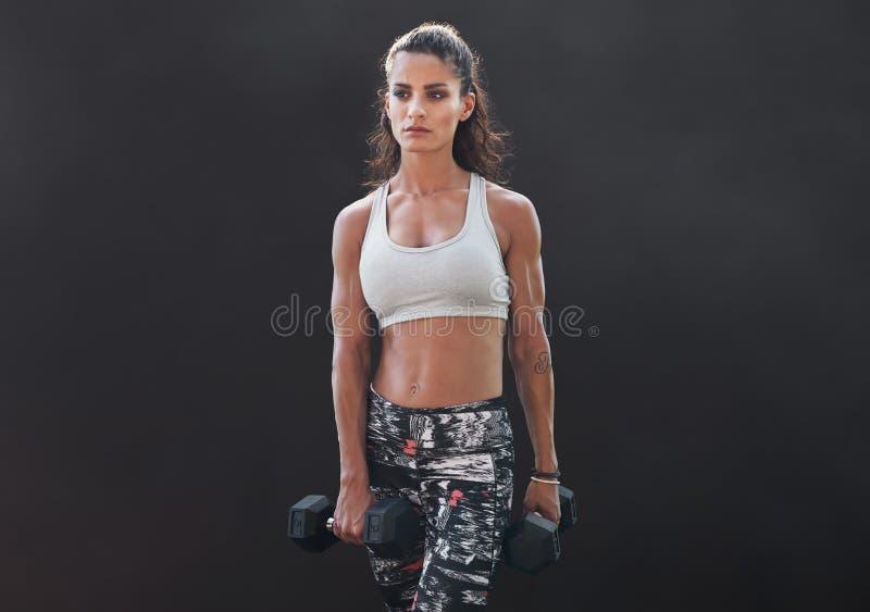 Kvinnlig görande bodybuildingutbildning för kondition med vikter royaltyfria bilder