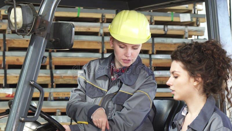 Kvinnlig gaffeltruckoperatör som talar till hennes kollega, medan arbeta fotografering för bildbyråer