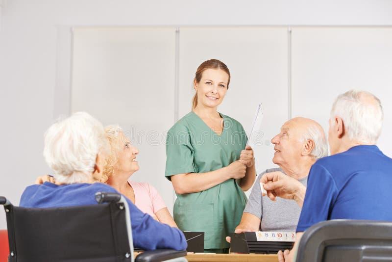 Kvinnlig geratric sjuksköterska med gruppen av pensionärer arkivbilder