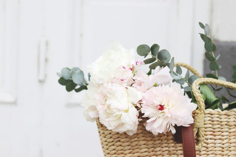 Kvinnlig gifta sig stillebensammans?ttning Straw French korgpåse med rosa pionblommor och eukalyptusbuketten gammalt royaltyfri bild