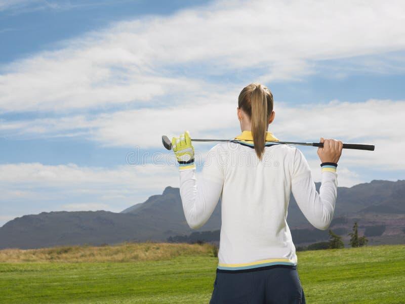 Kvinnlig golfare med klubban på golfbana arkivfoto