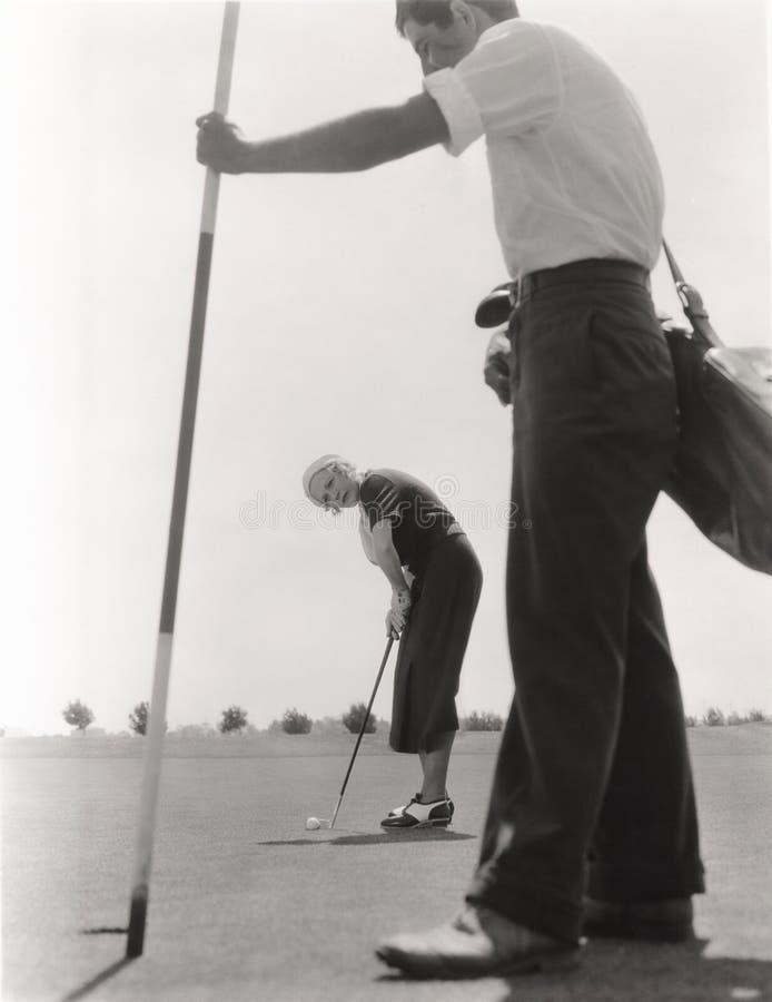 Kvinnlig golfare och hennes teburk arkivbilder