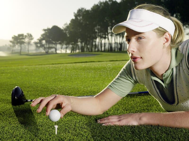 Kvinnlig golfare som förlägger bollen på utslagsplats royaltyfria bilder