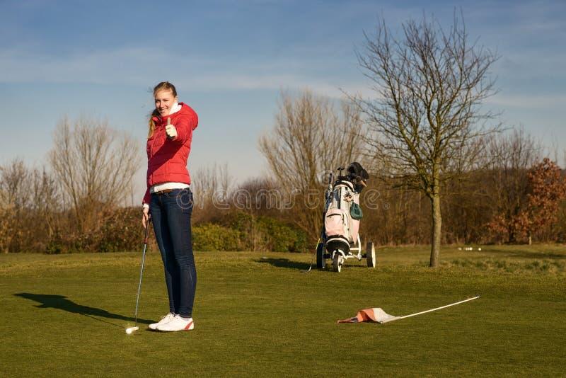 Kvinnlig golfare som ger upp tummar fotografering för bildbyråer