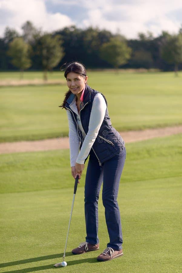 Kvinnlig golfare som sätter på gräsplan arkivbild
