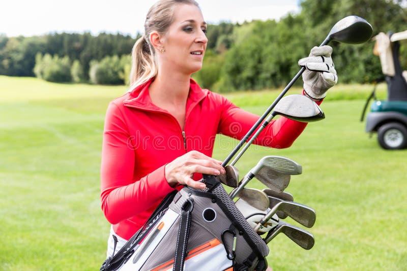 Kvinnlig golfare som väljer golfklubben arkivbild
