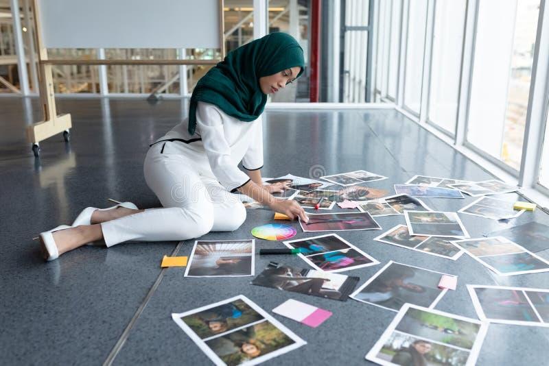 Kvinnlig grafisk formgivare i hijab som i regeringsställning kontrollerar fotografier arkivfoton