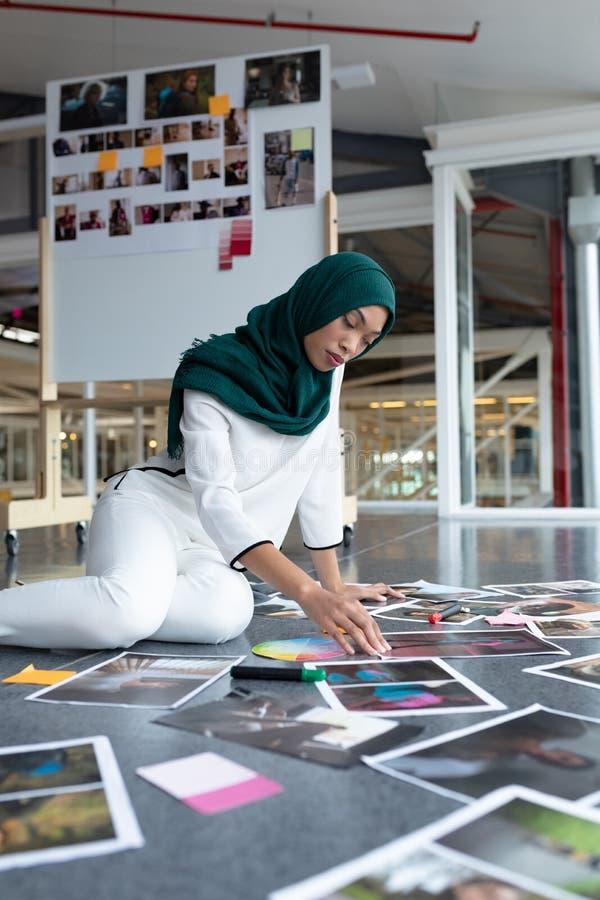 Kvinnlig grafisk formgivare i hijab som i regeringsställning kontrollerar fotografier royaltyfria bilder