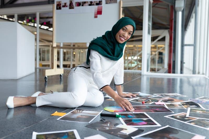Kvinnlig grafisk formgivare i hijab som i regeringsställning kontrollerar fotografier arkivfoto