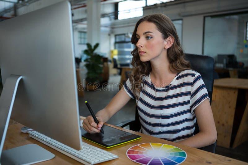 Kvinnlig grafisk formgivare som använder diagramminnestavlan på skrivbordet arkivfoton